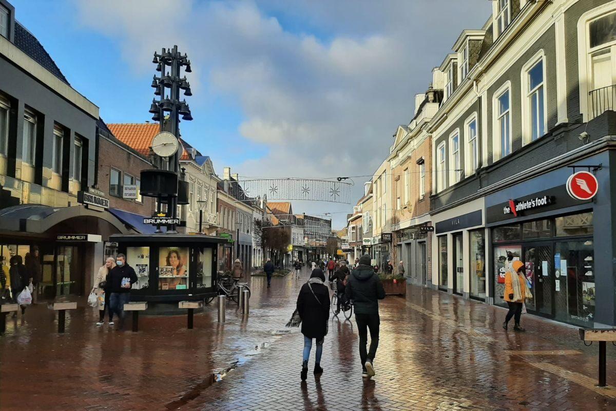 Grotestraat met winkels en mensen Almelo
