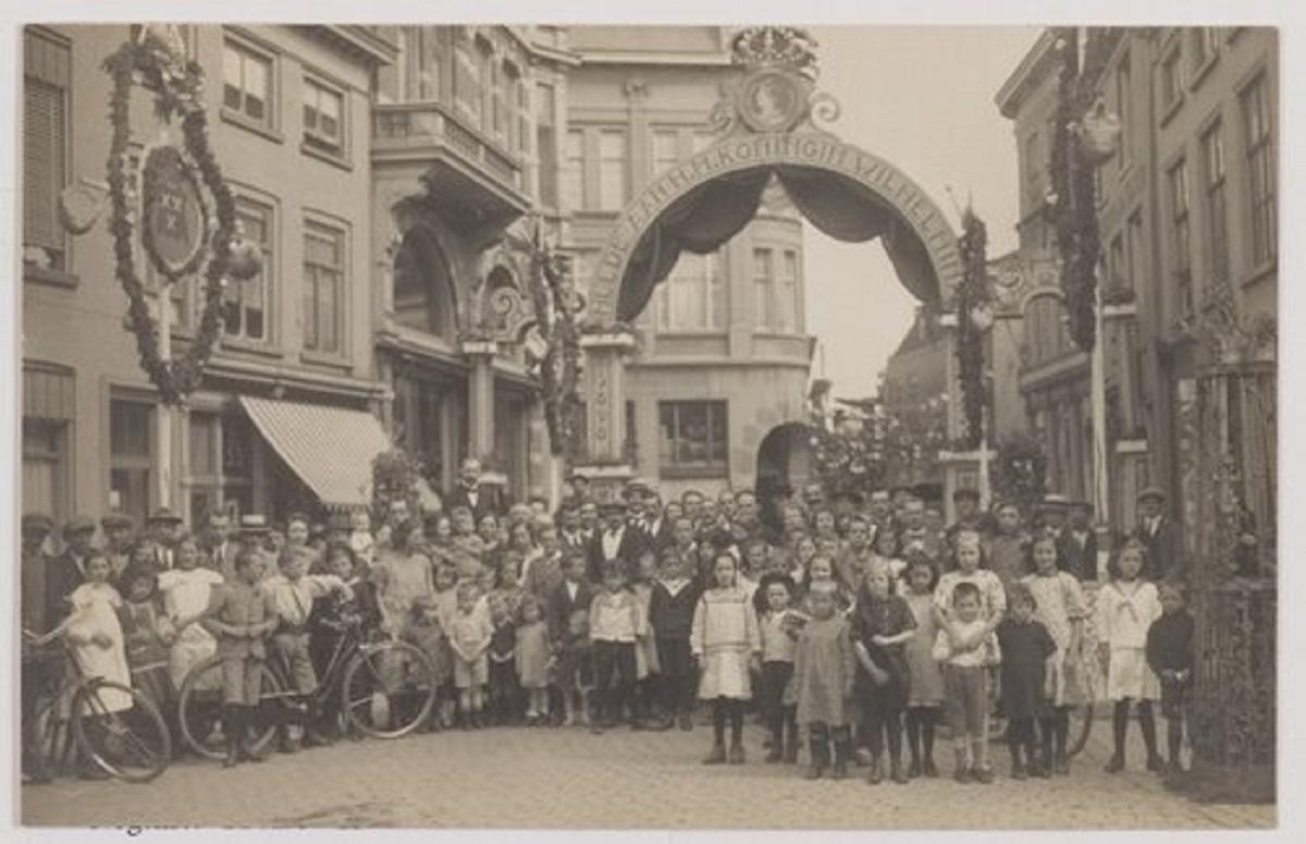 Bergen op Zoom: Lievevrouwestraat; links Mariahoek op de hoek Steenbergsestraat, Kortemeestraat en Fortuinstraat, erepoort ter gelegenheid van het 25 jarig regeringsjubileum van Koningin Wilhelmina (1890-1948) organiseerde men buurtfeesten en werd de straat versierd.