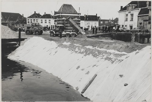 Bergen op Zoom: Demping van de haven tussen de spiritusfabriek en de Vissershaven. Werkzaamheden bij De Ham, op de achtergrond de Noordzijde Haven. Laadschop van Bakx transport, machinist Sjef de Meier en vrachtwagen van Stouthart transport.