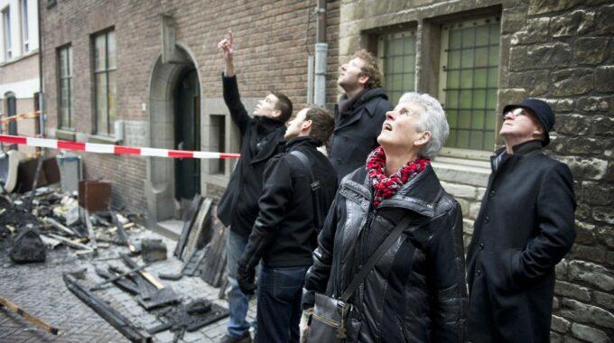 BERGEN OP ZOOM - Voorbijgangers kijken naar het monumentale hotel De Draak dat is getroffen door brand. Er ontstond de nodige schade aan het hotel, dat oorspronkelijk stamt uit de middeleeuwen en later een aantal keren is herbouwd. ANP KOEN VERHEIJDEN