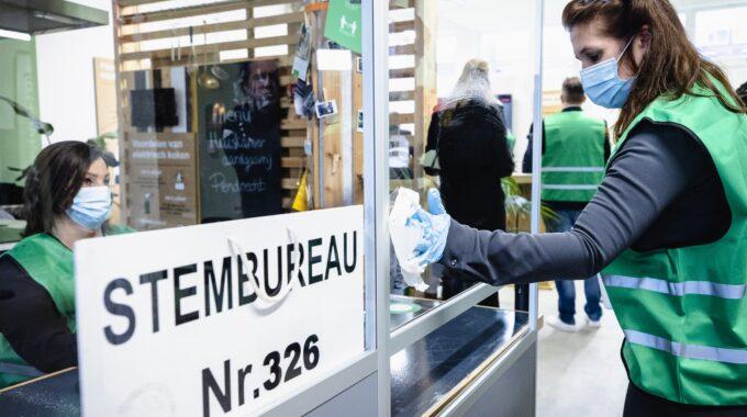 Een model-stembureau in Rotterdam Charlois wordt gedesinfecteerd. Voor de Tweede Kamerverkiezingen moeten alle stembureaus coronaproof worden ingericht. ANP SEM VAN DER WAL