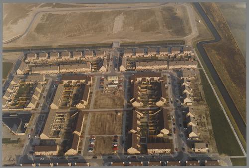 Luchtopname gezien naar het luchtfoto's Bergen op Zoom noorden. Onderaan Ruigewerve en er omheen de in aanbouw zijnde Bergse Plaat. Bovenaan de onbebouwde Ansjovislaan aan de Binneschelde. De vliegenier bij deze luchtopname is Dhr. H. v.d. Bogart. 1991