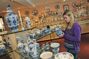 Bezoeker bekijkt Delfts Blauw in de Delftse Pauw