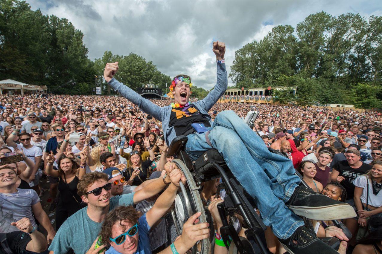 2016-08-28 15:40:55 HAARLEMMERMEER - Een jongen in een rolstoel wordt boven het publiek getild bij het optreden van de Jeugd van Tegenwoordig tijdens de 23e editie van het dancefestival Mysteryland. ANP KIPPA FERDY DAMMAN