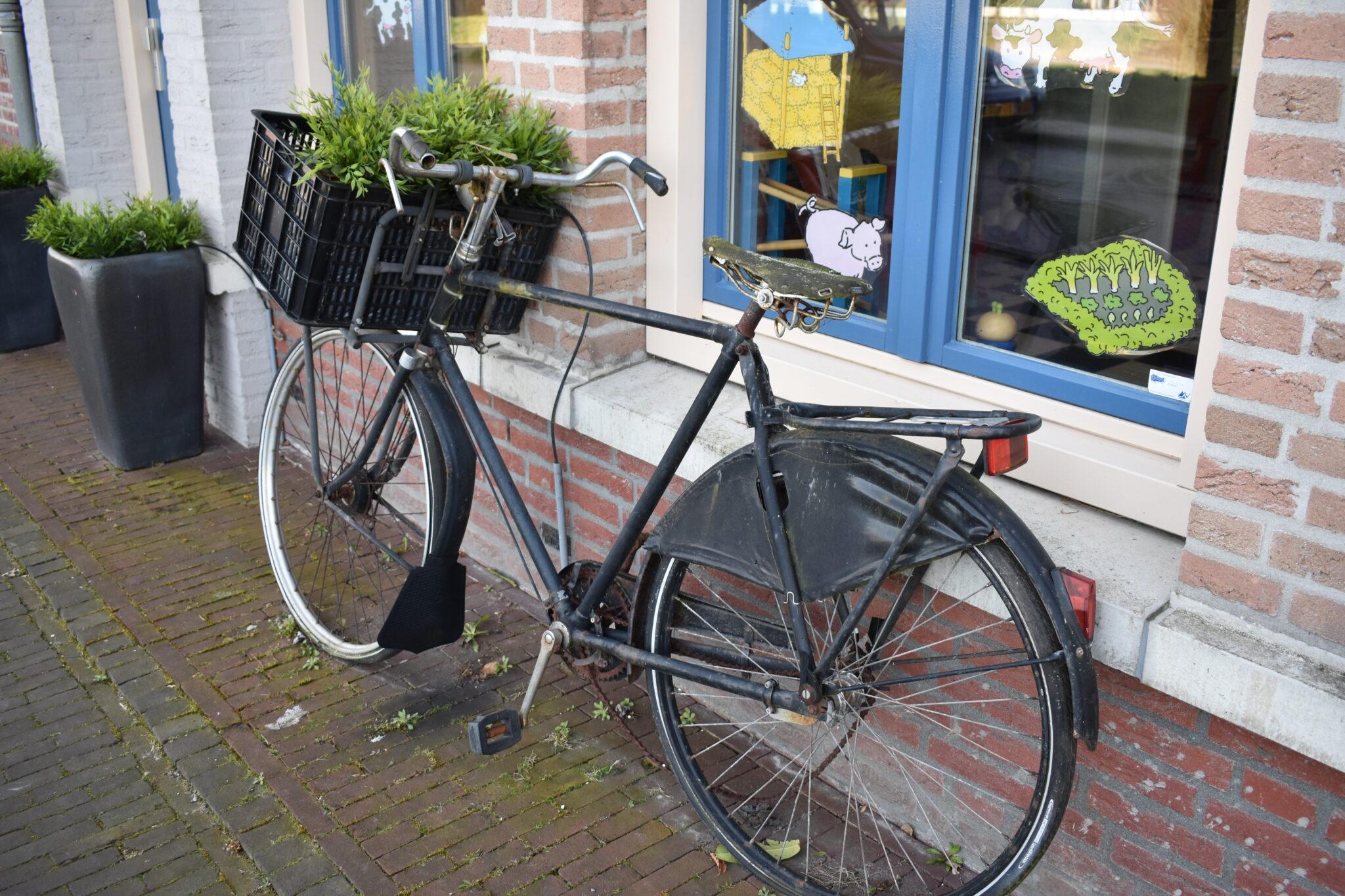 Een oude fiets tegen een gevel in Brandevoort