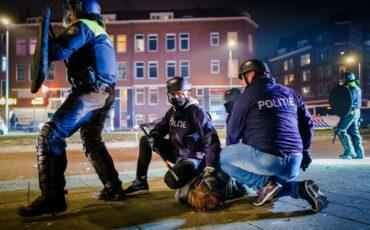 Politie arresteert een man tijdens de rellen.