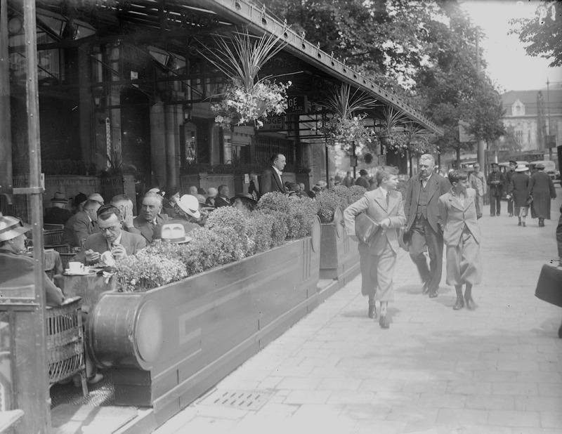 De Coolsingel met voetgangers en mensen op het terras.